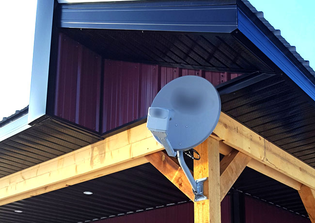 a satellite dish mounted on the front of a building